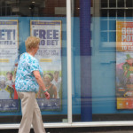 woman walking past a betting shop by Amy Hopwood